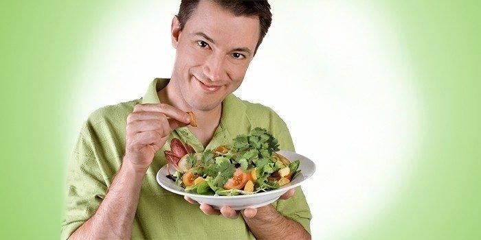 Мужчина держит тарелку с овощным салатом