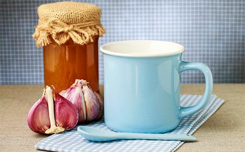 Кружка, чеснок и банка с медом на столе