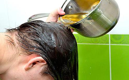 Девушка льёт на волосы травяной отвар из ковшика