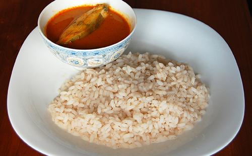 Вареный рис на блюде и крохотная рыбка