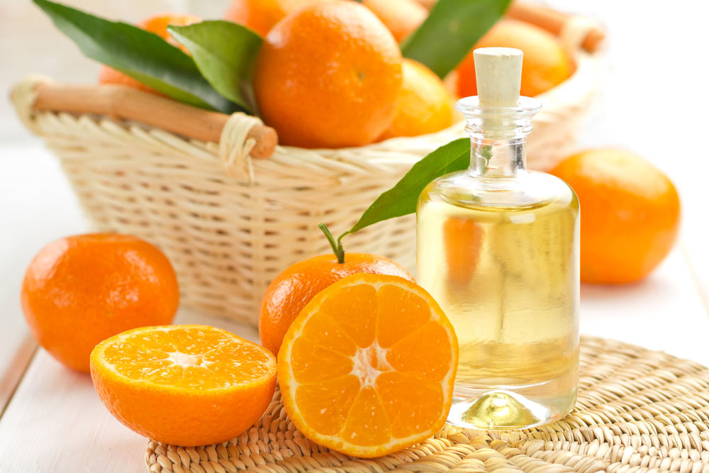Апельсиновое масло в прозрачном флаконе и мандарины