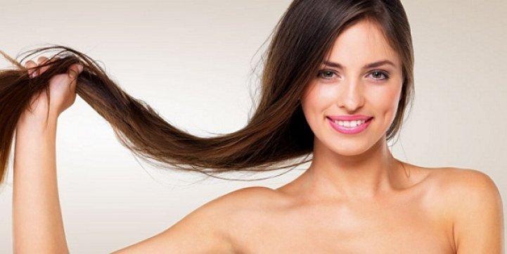 Девушка улыбаясь держит свои волосы