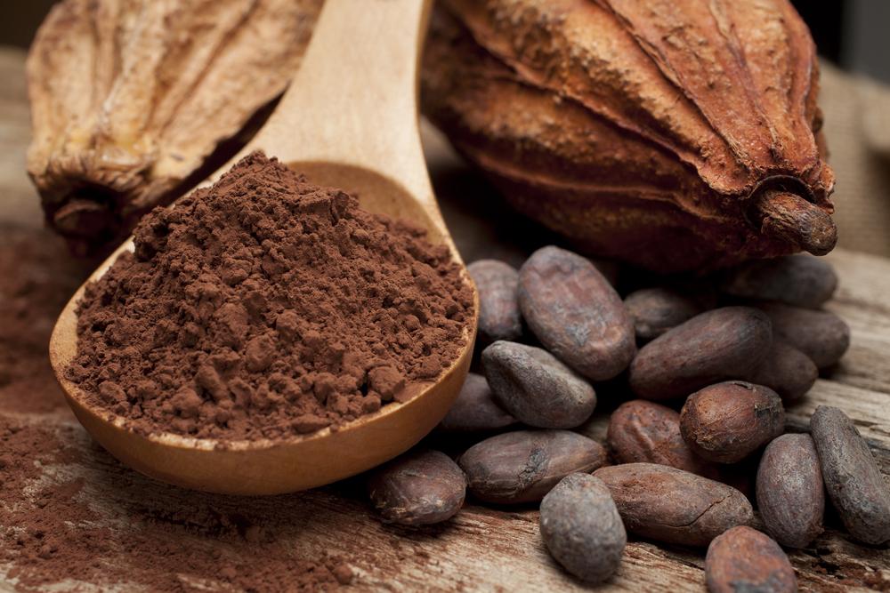 Какао-порошок в деревянной ложке и бобы
