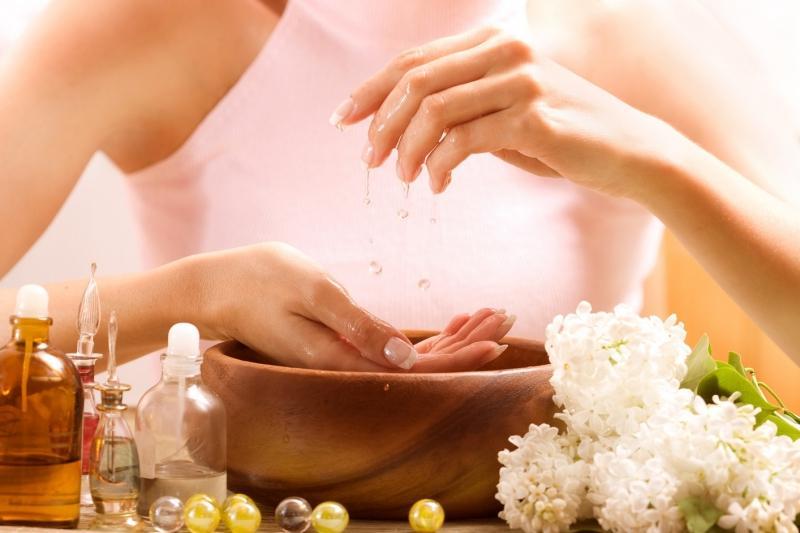 Руки девушки и ванночка для ногтей